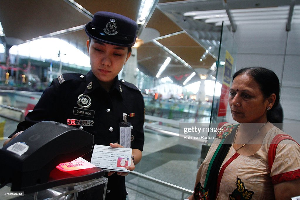 A female Malaysian Royal Police officer scans a passenger's ticket at the departure gate in Kuala Lumpur International Airport on March 20, 2014 in Kuala Lumpur, Malaysia. Australian authorities today received satellite imagery that shows two large objects in the Indian Ocean that may be debris from missing Malaysia Airlines flight MH370. The airliner went missing nearly two weeks ago carrying 239 passengers and crew on route from Kuala Lumpur to Beijing.