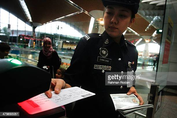 A female Malaysian Royal Police officer scans a passenger's ticket at the departure gate in Kuala Lumpur International Airport on March 20 2014 in...