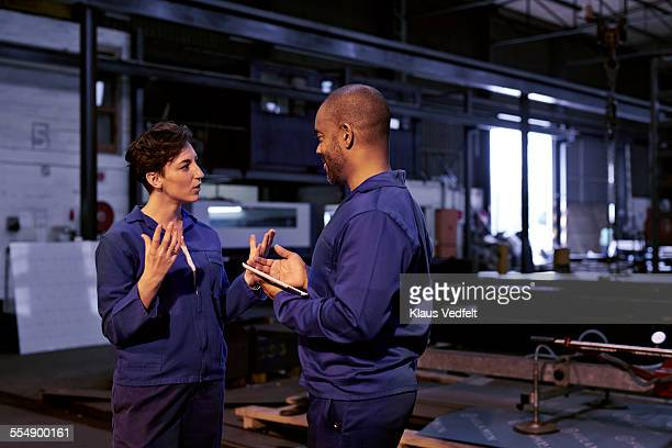 Female & male steel working discussing at factory
