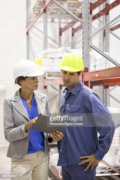Female manager speaking with warehouse worker