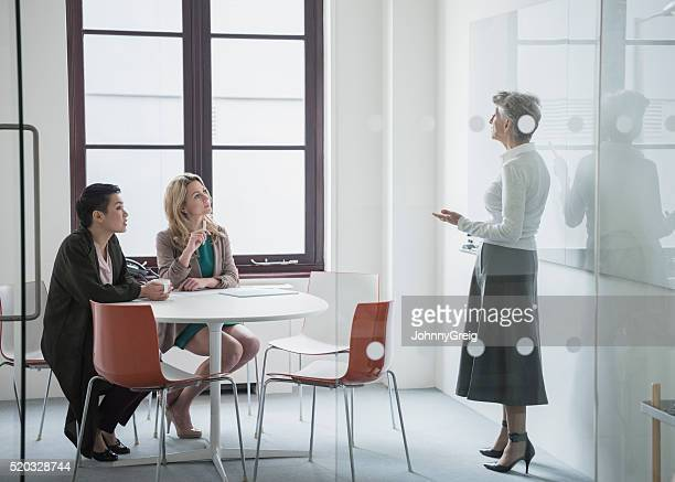 Female manager talking to colleagues behind office partition