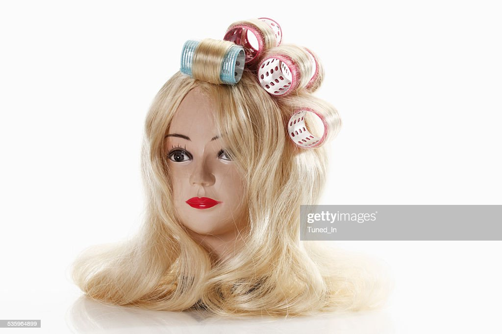 Female mannequin head wearing blonde wig with curlers : Stock Photo