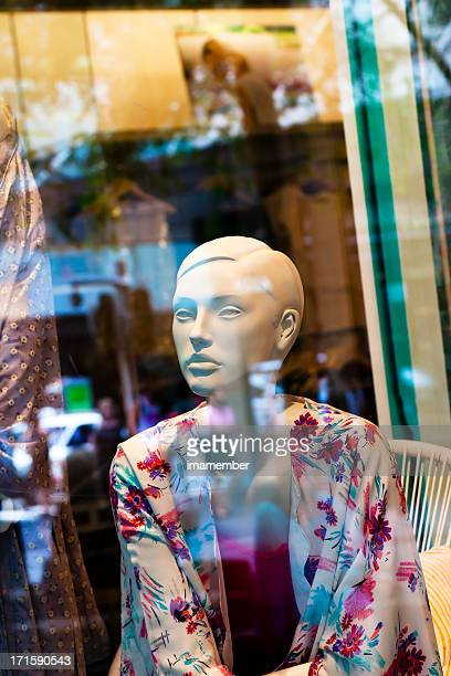 Female mannequin in shop window with street reflection
