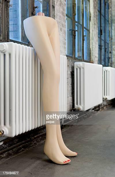 female mannequin legs standing against radiator