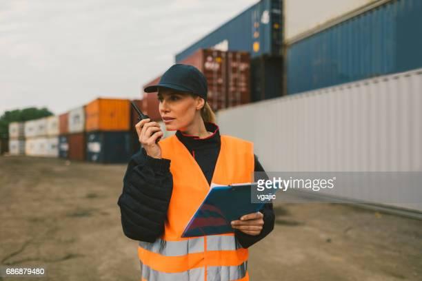 Weibliche Arbeiter überprüfen Frachtcontainer