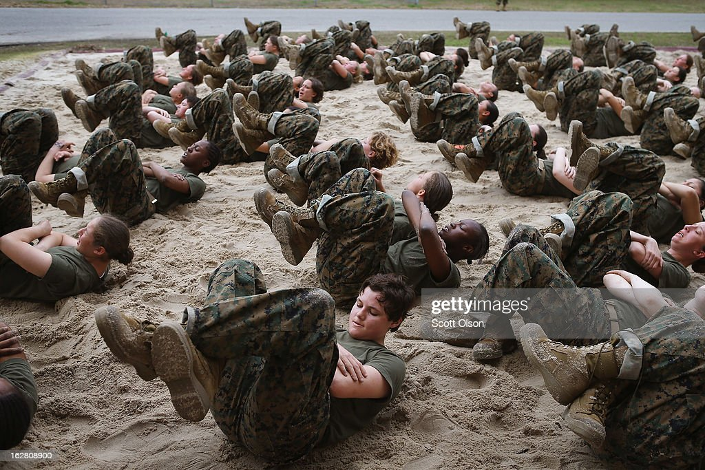 Female Marine recruits are disciplined with some unscheduled physical training in the sand pit outside their barracks during boot camp February 27...