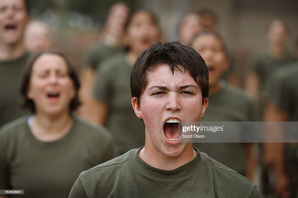 Female Marine recruits respond to their drill instructor as they are disciplined with some unscheduled physical training in the sand pit outside...