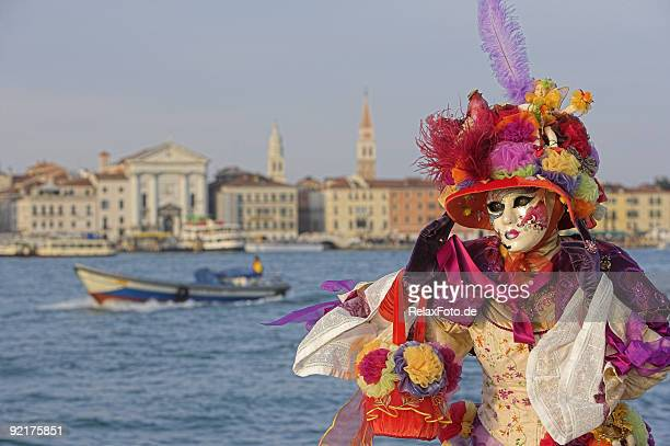 Female mask with colorful costume at Grand Canal in Venice