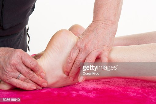 Female masseuse giving a foot massage to man : Stock Photo
