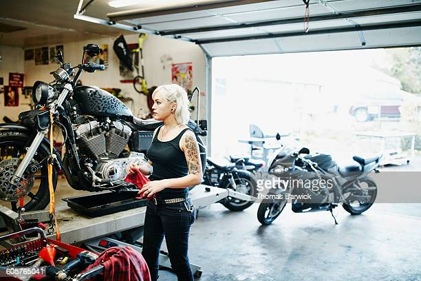Female mechanic changing oil of motorcycle on lift