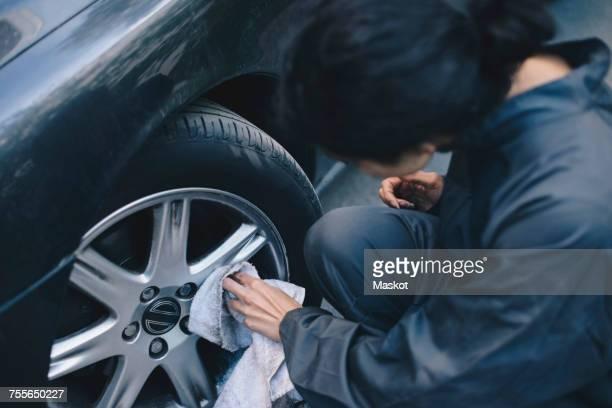 Female mechanic cleaning car wheel rim outside auto repair shop