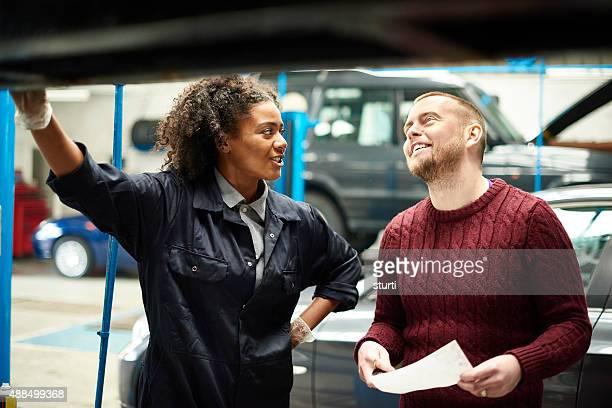 female mechanic explains bill to customer
