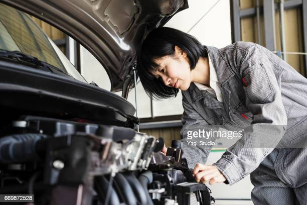 Female mechanic fixing a damaged car in an auto repair shop