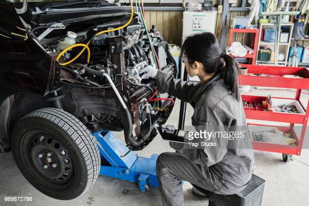 Female mechanic inspecting a damaged car with digital tablet in an auto repair garage