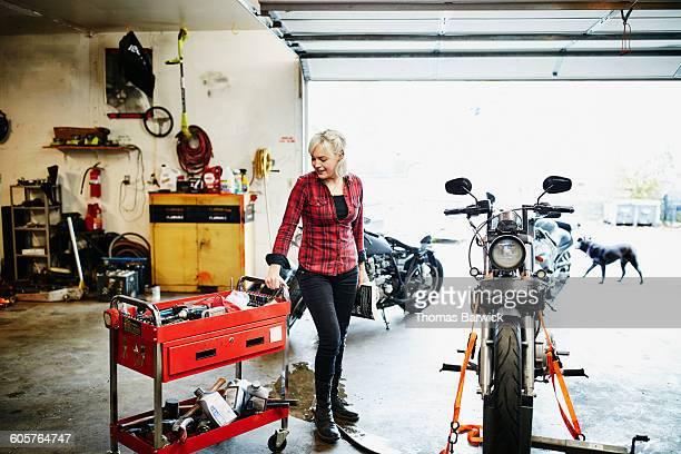 Female mechanic preparing to work on motorcycle