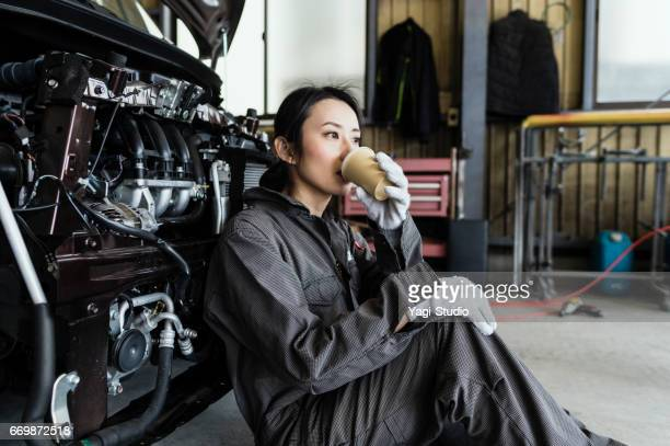 Female mechanic resting in an automotive repair shop