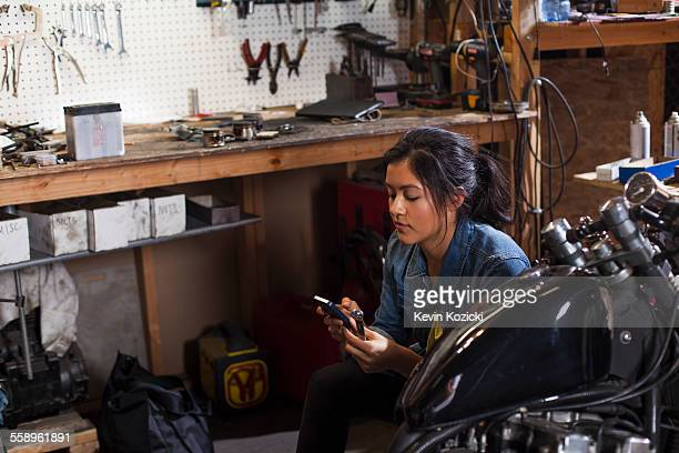 Female mechanic using mobile phone in workshop