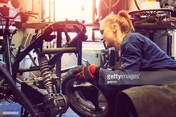 Female mechanic working on a custom motorbike