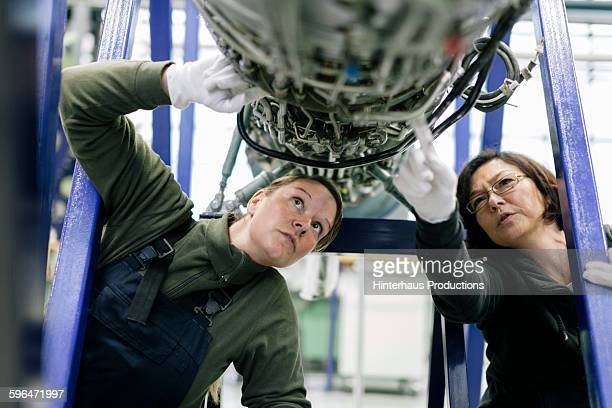 Female mechanics examine an aircraft engine.