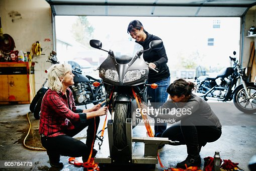 Female mechanics strapping motorcycle to lift