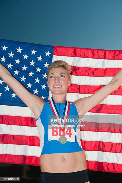 Female medal winner holding up American flag in victory