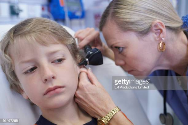 Female medical professional examining boy