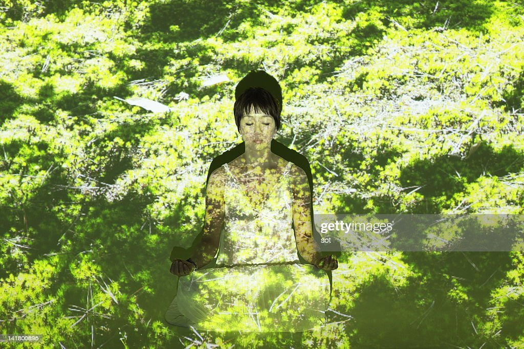 Female meditating in the moss : Stock Photo