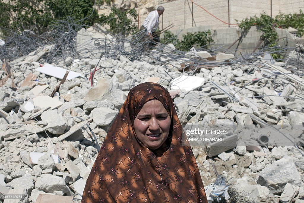 A female member of the Palestinian Ghaith family stands with the rubble of her home to her back after it was demolished by Jerusalem municipality workers in the mostly Arab east Jerusalem neighbourhood of al-Tur on April 29, 2013. Palestinian homes built without an Israeli construction permit are often demolished by order of the Jerusalem municipality.