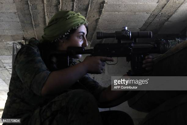 TOPSHOT A female member of the Syrian Democratic Forces a US backed KurdishArab alliance holds a position inside a building in an area close to the...