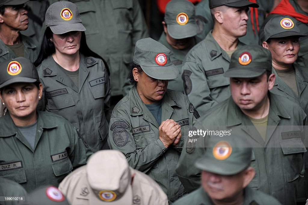 Female members of de Venezuelan Militia pray for Venezuelan President Hugo Chavez's health outside the National Assembly in Caracas on January 5, 2013. Venezuelan lawmakers gathered Saturday for a key leadership vote and debate as President Hugo Chavez's battle with cancer appeared almost certain to delay his swearing-in for a new six year term. AFP PHOTO/Leo Ramirez