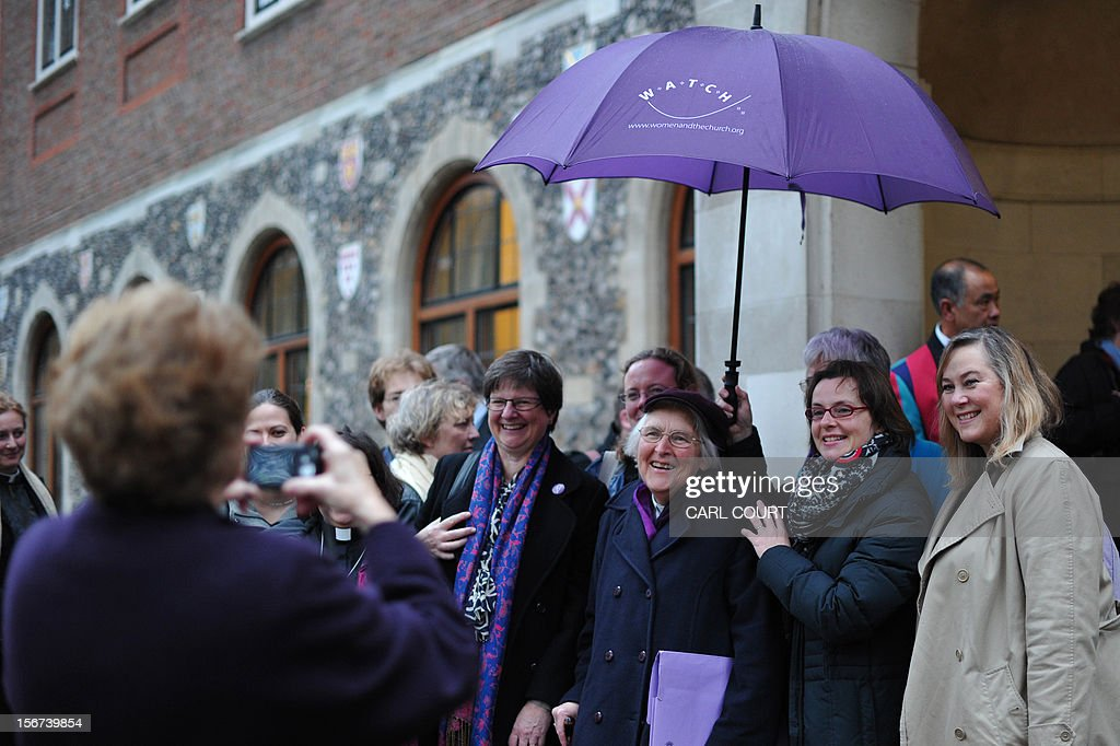 Female members of the clergy and visitors pose for a photograph taken by a friend as they wait to enter the venue of the three-day Church of England General Synod in central London on November 20, 2012, during which there will be a vote on whether to allow women to become bishops. The 470-member General Synod will vote on November 20 on the issue of women bishops which has split traditionalists and liberals, two decades after England's established state Church backed the introduction of women priests. AFP PHOTO / CARL COURT