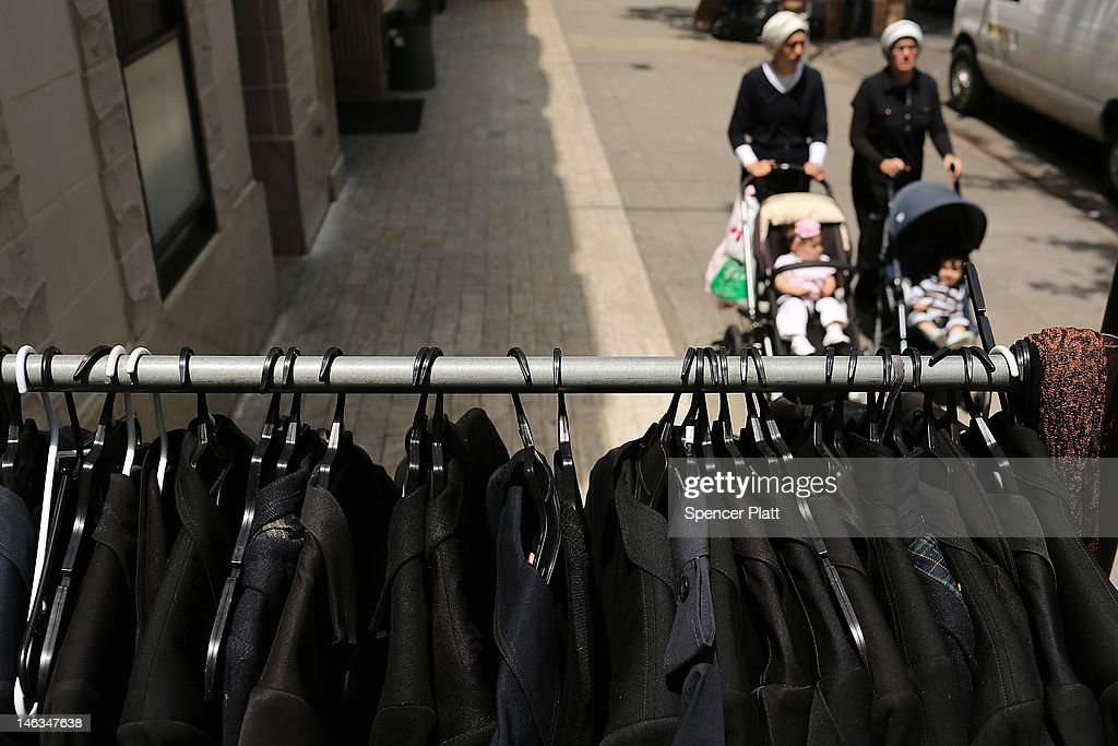 Female members of the Jewish Orthodox community walk by Orthodox mens jackets on a street in a Brooklyn neighborhood on June 14 2012 in New York City...