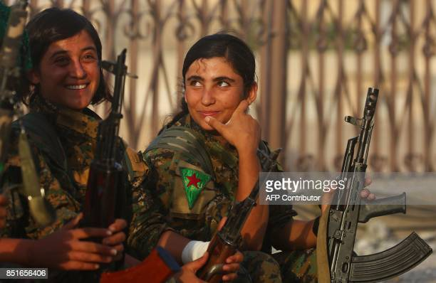 Female members of the Syrian Democratic Forces sit on a street in the former Islamic State stronghold of Raqa on September 22 2017 The USbacked...