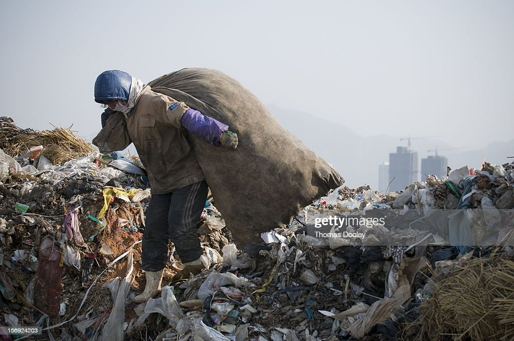 A female migrant worker from Henan province is carrying a large bag of plastic bottles she has collected at the Dalian Jinzhou garbage dump. China does not have a recycling infrastructure in many major cities. Many migrant workers search garbage dumps like this one for anything that can be sold. Dalian, China 10 January 2008.