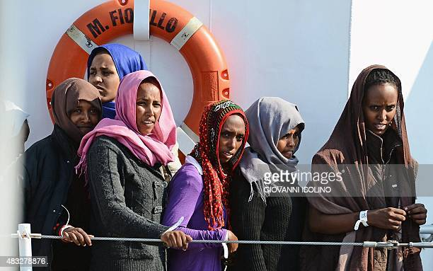 Female migrants stand on the patrol vessel Fiorillo of the Italian Coast Guard as it arrives in the port of Pozzallo on August 7 2015 after saving...