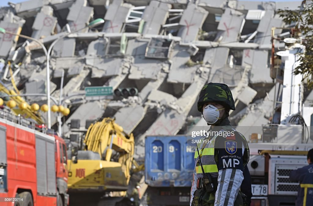 A female military police officer stands guard in front of the collapsed Wei-Kuan complex in Tainan, southern Taiwan, on February 9, 2016. Rescuers deployed heavy machinery in a renewed effort to locate more than 100 people trapped in the rubble of a Taiwan apartment complex felled by an earthquake as the 72-hour 'golden window' for finding survivors passed. AFP PHOTO / Sam Yeh / AFP / SAM YEH