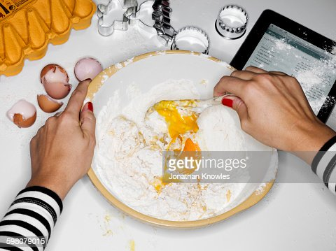 Female mixing flour with eggs, tablet on table
