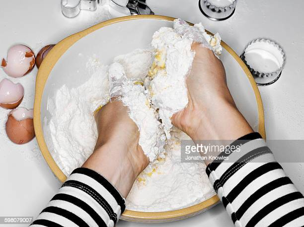 Female mixing flour with eggs with hands