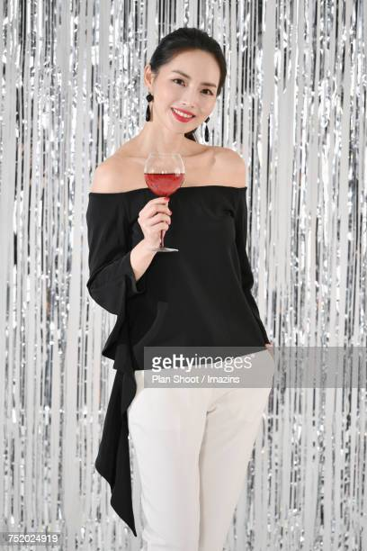 Female model holding a wine glass