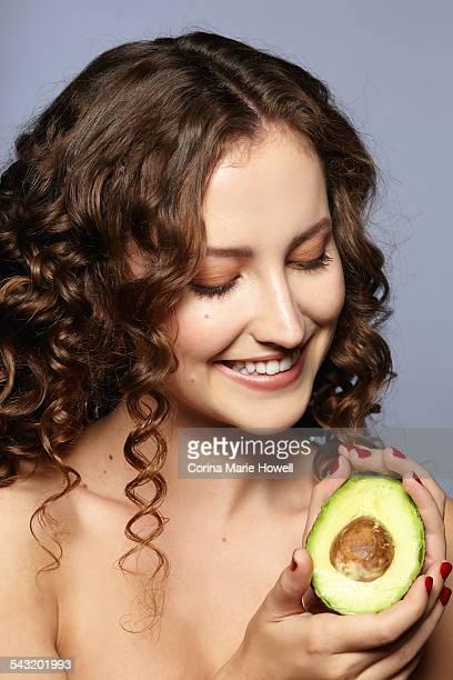 Female model holding halved avocado
