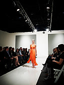 Female model in gown walking down catwalk