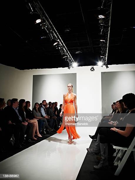 Female model in gown walking down catwalk