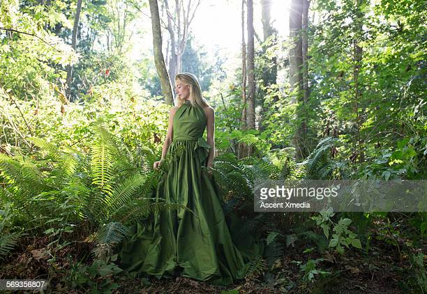 Female model pauses in lush forest, contemplative