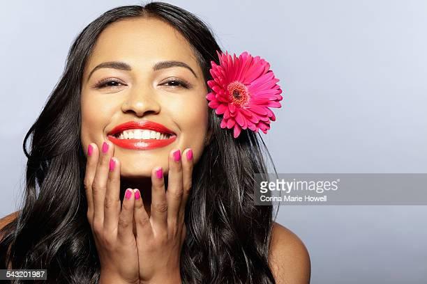 Female model smiling, flower on hair