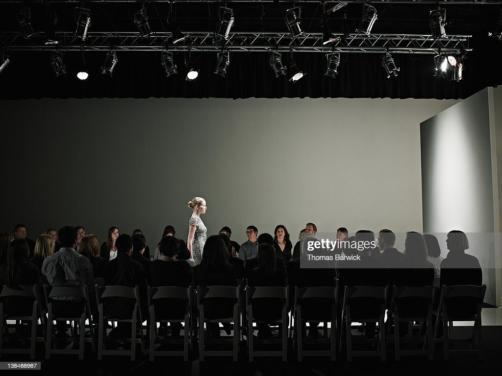 Female model walking alone on catwalk : Stock Photo