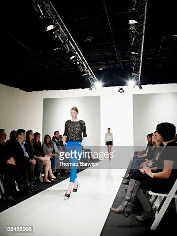 Female model walking down catwalk at fashion show : Stock Photo