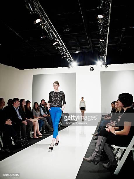 Female model walking down catwalk at fashion show