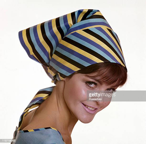 A female model wearing a striped scarf as a headpiece tied at the back complemented by piping on her dress in a studio setting in London circa 1964