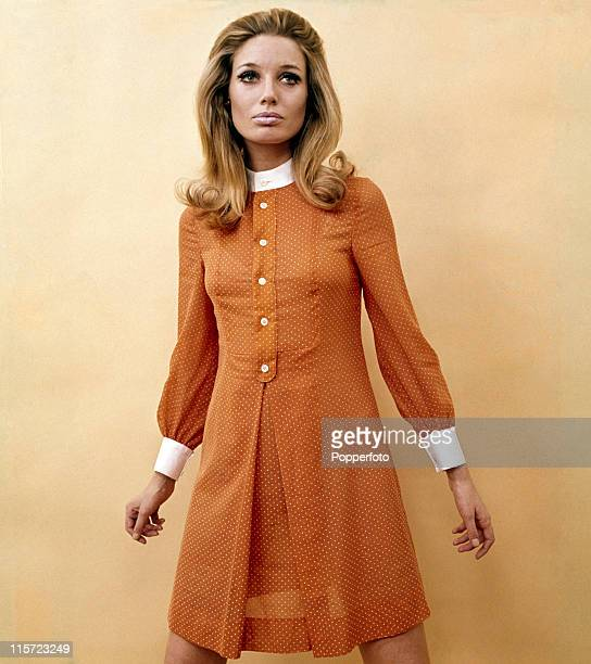 A female model with long blonde hair wearing an orange dress with white polkadots collar cuffs and buttons and standing with slightly raised arms in...