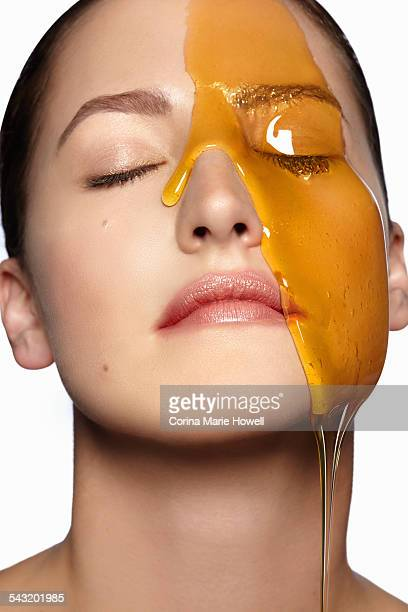 Female models face partially covered in honey